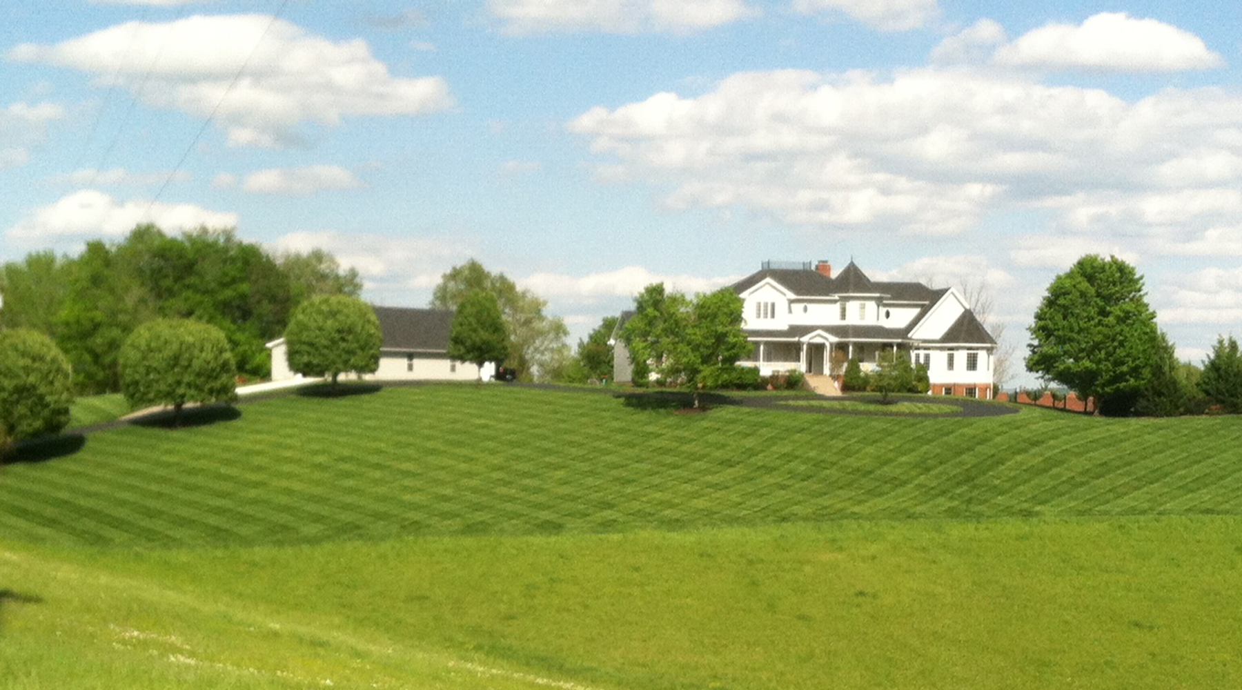 Picture of a large house on a hill with diamond patterns cut into the grass.