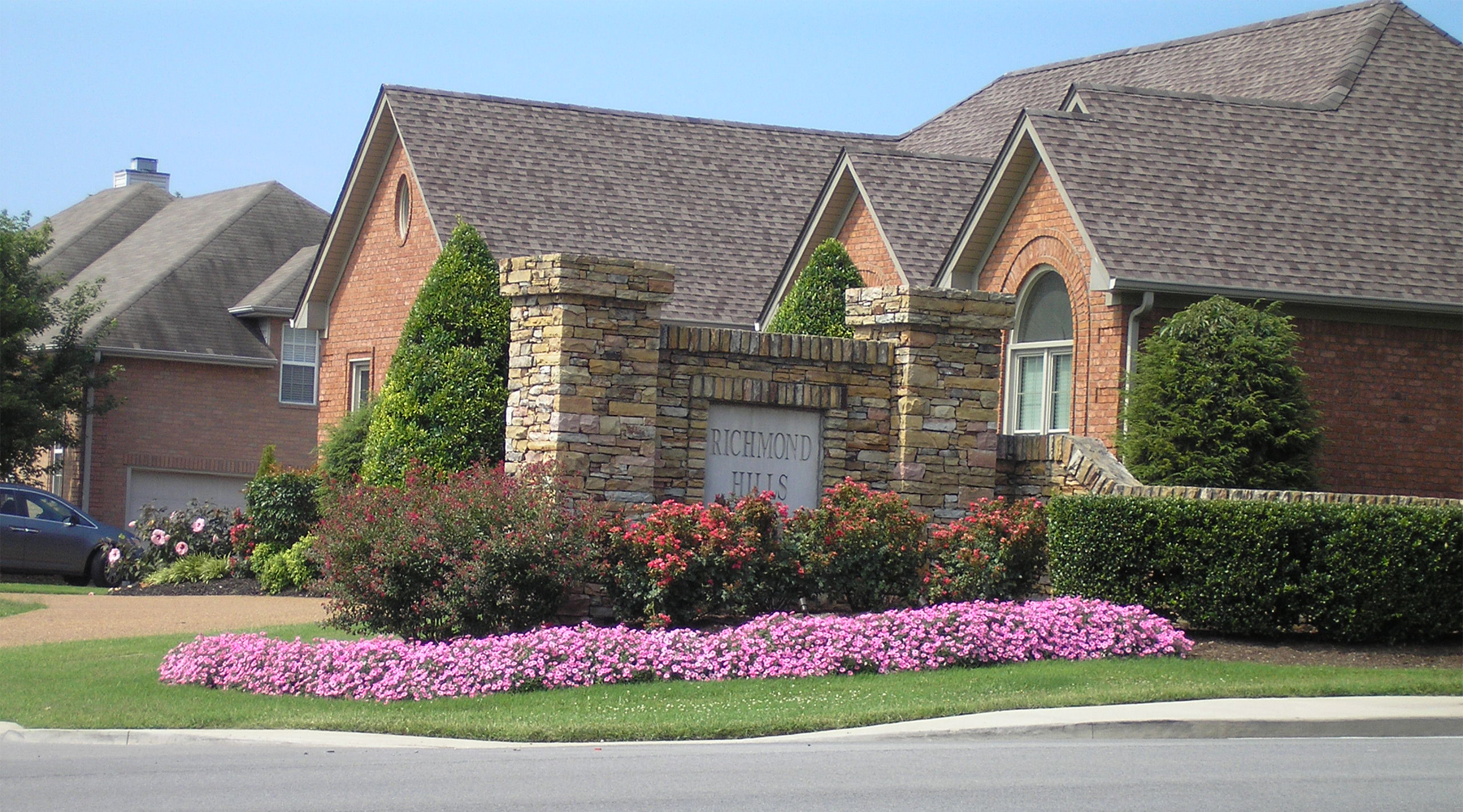 Picture of a stone neighborhood sign surrounded by pink flowers and red bushes.