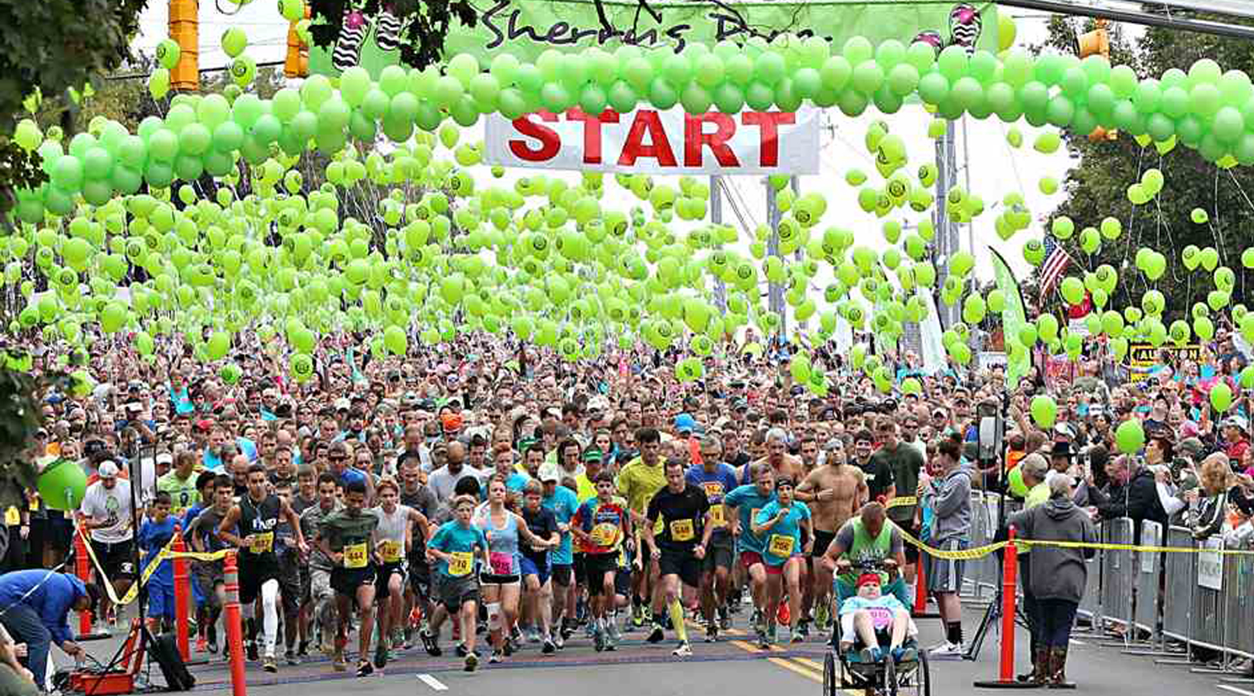 Picture of the starting line of a marathon with lime green balloons surrounding the runners.